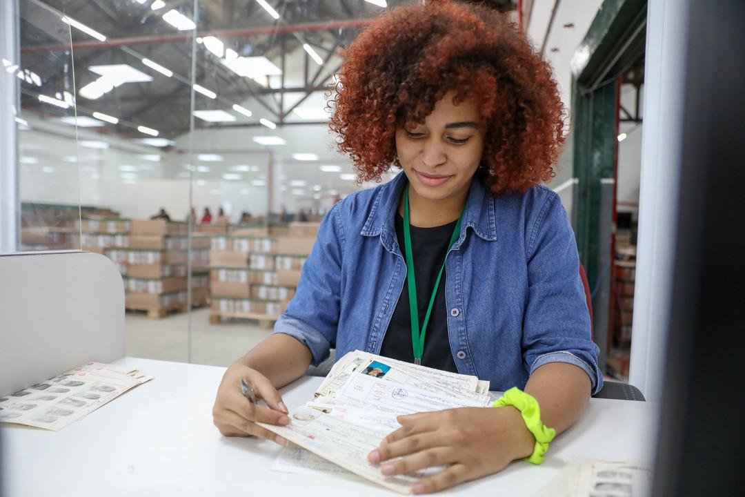 Gestão de documentos: mulher mexendo em um bloco de papéis