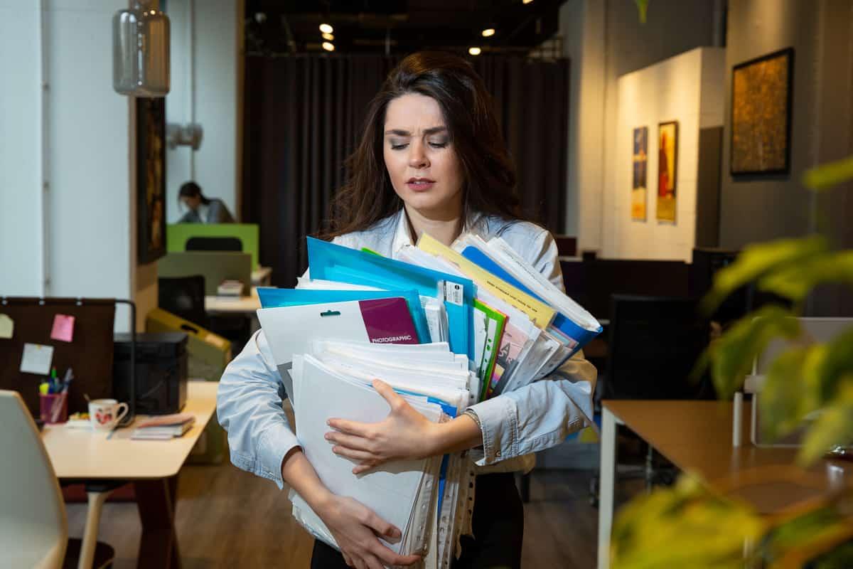 Mulher segura pilha de documentos com as mãos.