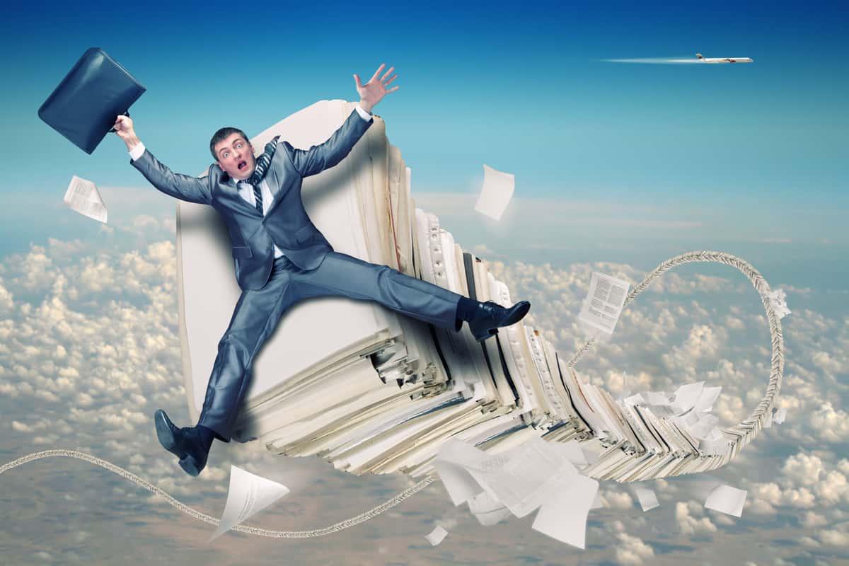 Indexação de documentos: homem voando pelos ares ejetado por uma pilha de arquivos.