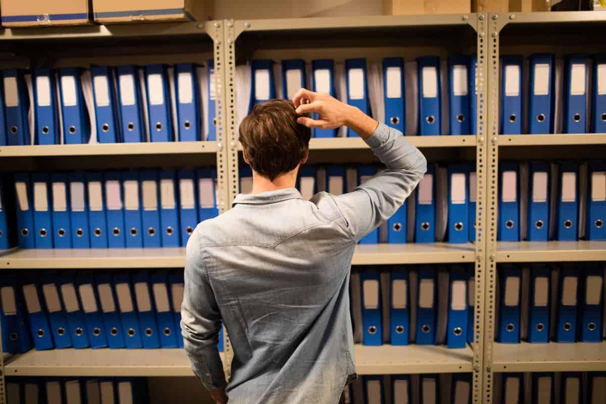 Outsourcing: homem de costas olhando para prateleira de arquivos.
