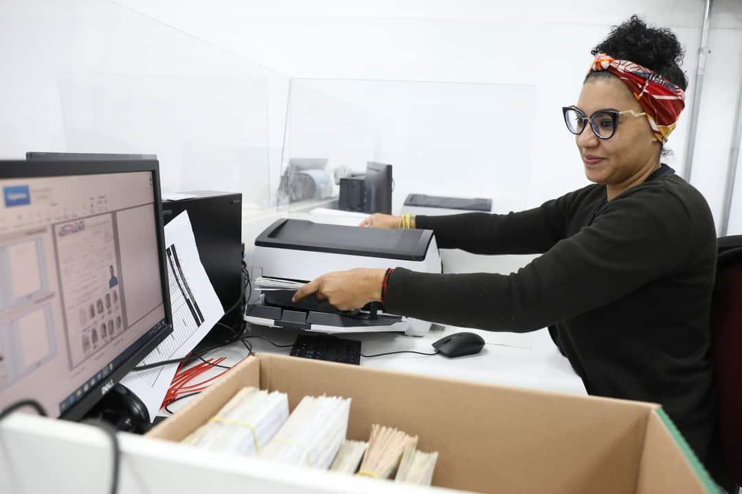 Documentos digitais x físicos: mulher manipula impressora enquanto olha tela do computador.