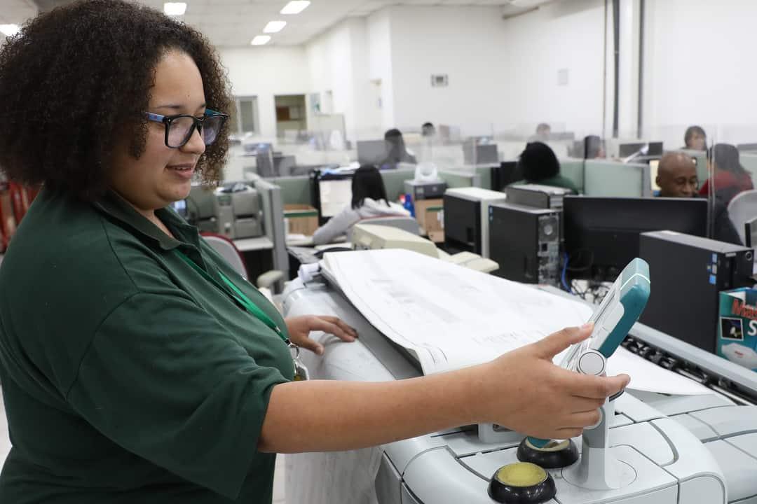 Transformação digital: mulher utiliza equipamento para escanear documentos.