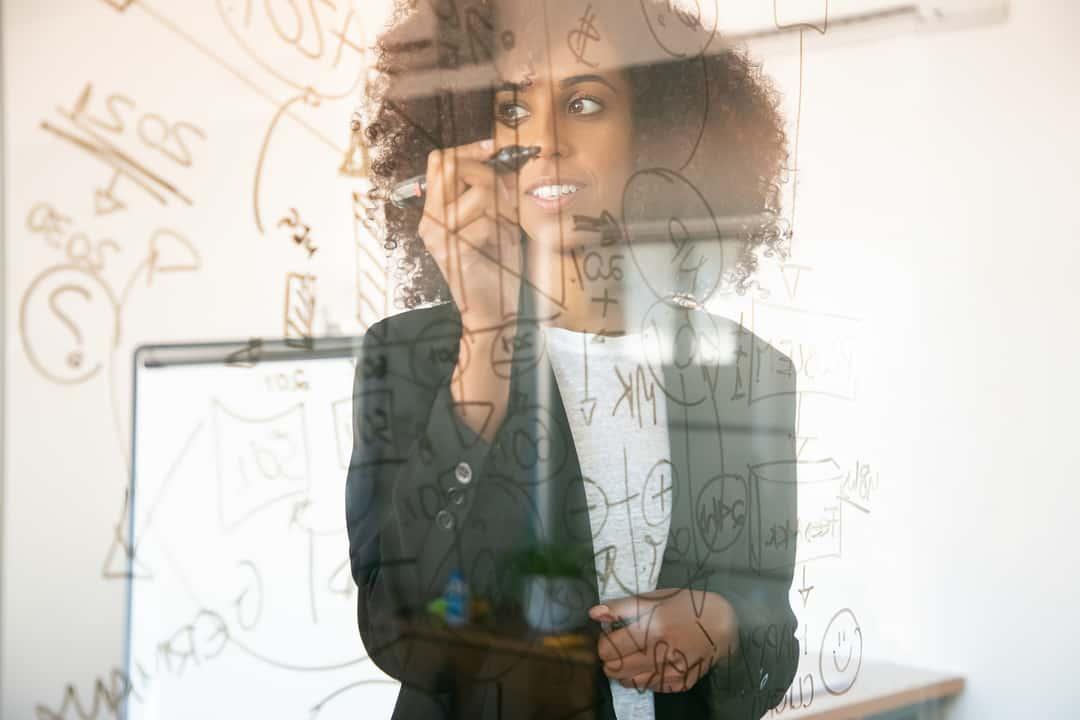ECM: jovem mulher escreve planejamento em lousa de vidro.