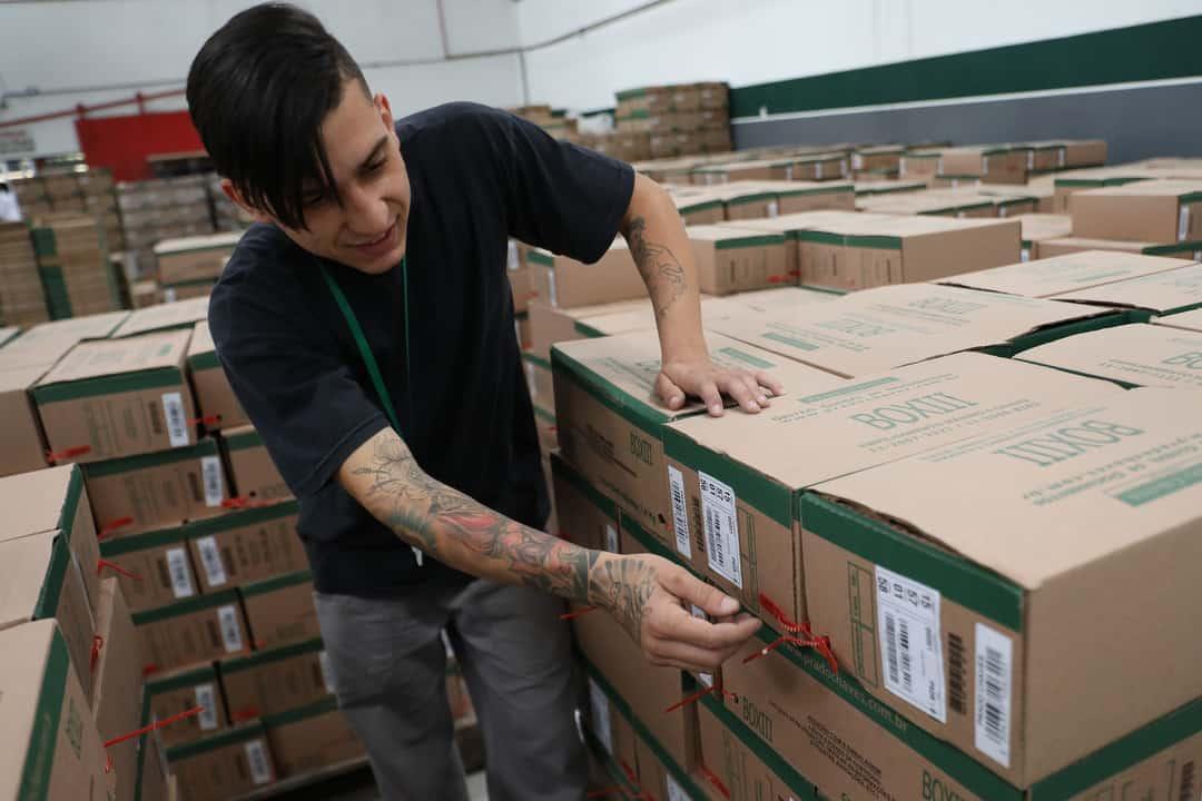 O que é tipificação: homem tipifica caixa com documentos.