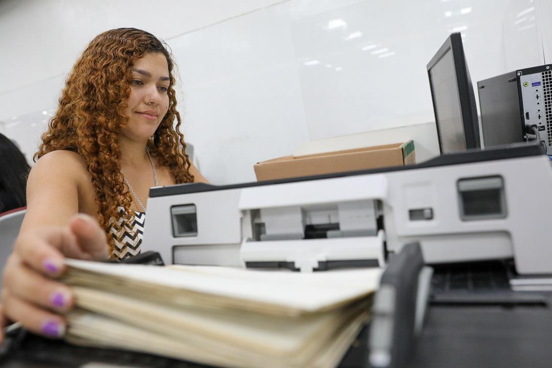 Como arquivar documentos de RH: mulher trabalhando em escritório.