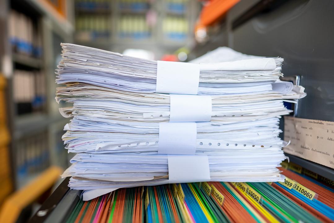 Destruição de documentos: pilha de documentos sobre arquivo colorido.