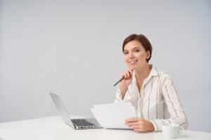 Formalizar documentação: jovem mulher sentada com documentos e caneta nas mãos.