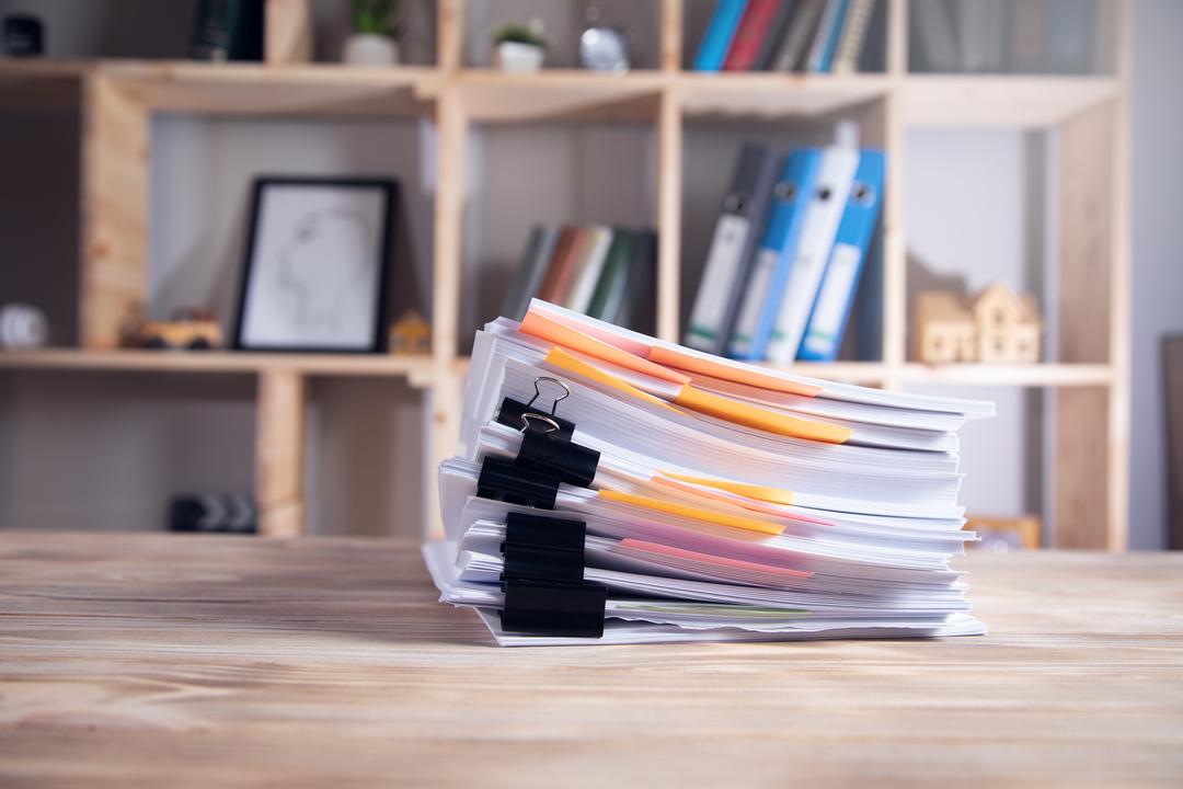 Redução de custos: pilha de documentos sobre a mesa.