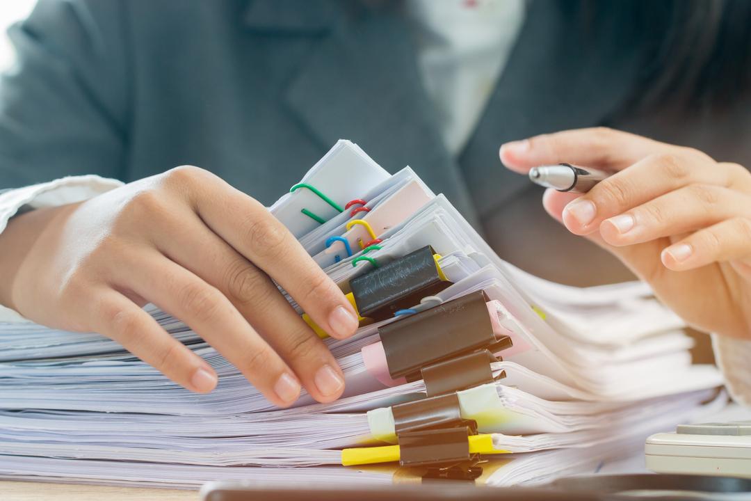 Gestão de documentos: mão com uma caneta entre os dedos, segurando bloco de folhas brancas.