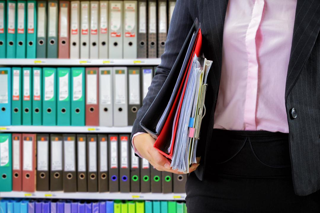 Mulher segurando pastas na frente de uma estante de ficheiros com documentos