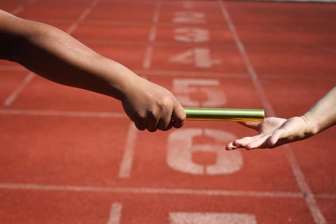pessoa passando bastão para outra em pista de corrida para simular metáfora do hand-off