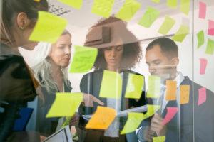 pessoas na frente de uma lousa com post-its conversando sobre estratégias de 5W2H
