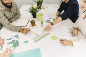 grupo conversando em escritório com plantas e documentos verdes sob a mesa para referenciar a gestão inteligente e sustentabilidade