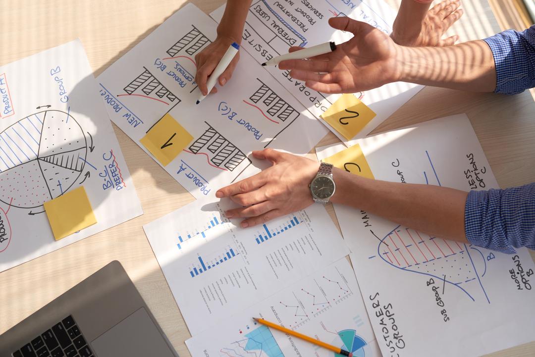 pessoas em escritório conversando sob gráficos fazendo alusão a otimização de processos