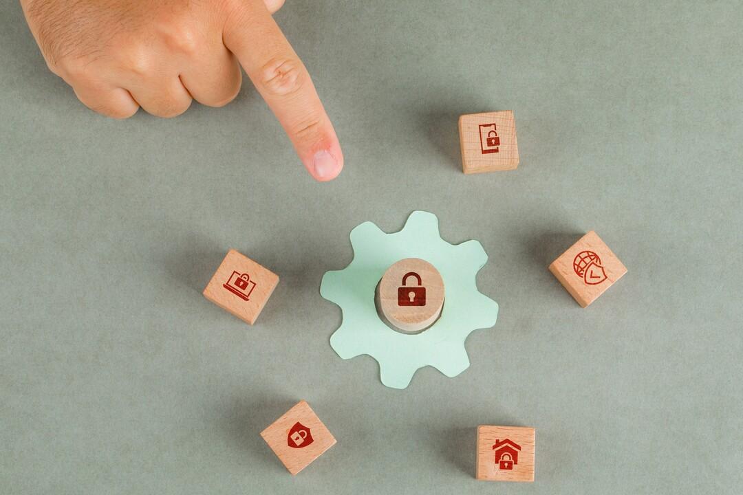 Integridade de dados: pessoa apontando com dedo para engrenagem ao lado de pequenos cubos de madeira