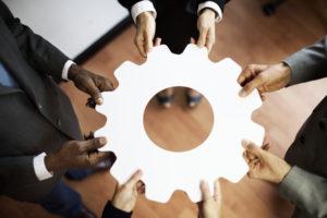 gerenciamento de processos: pessoas de diferentes etnias segurando em círculo uma engrenagem