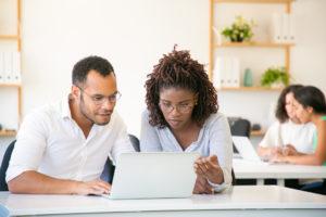 Digitalização do RH: homem e mulher sentados analisando perfil de candidato em um computador